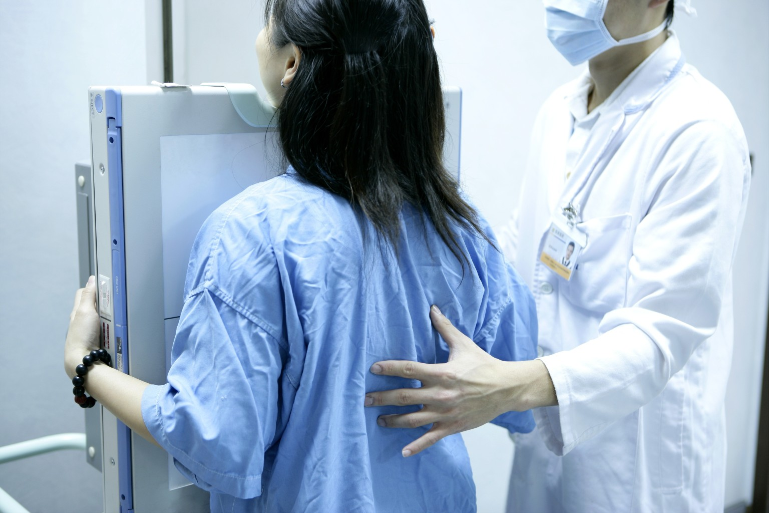 Technician assisting female patient with chest x-ray
